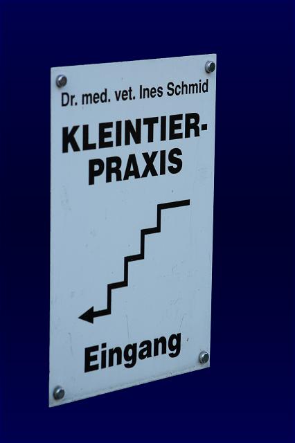Schild: Eingang Praxis über Treppe